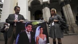 Na porta da Igreja Nossa Senhora da Paz, no Rio de Janeiro, José Macario e Maria Esther exibem cartaz com a foto do filho, Carlos Eduardo de Mello, e da mulher, Bianca Cota, mortos na queda do avião.