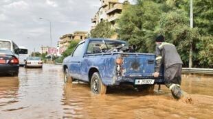 Un homme pousse un camion sur une autoroute inondée dans la région de Naameh, au sud de la capitale libanaise, le 5 décembre 2019.