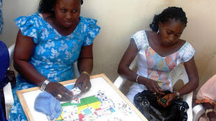 At the Khombole Health Centre, Coura and other young mothers play the W3 game