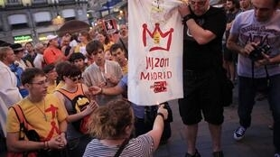 Pilgrims pray as protesters try to set a World Youth Day flag on fire