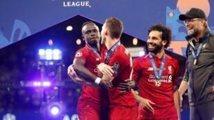 Le Sénégalais Sadio Mané (à gauche) et l'Egyptien Mohamed Salah (au centre) fêtent la victoire de Liverpool en Ligue des champions, avec Jürgen Klopp (à droite) et Andrew Robertson.