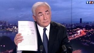 Dominique Strauss-Kahn brandishes the prosecutor's report during the interview