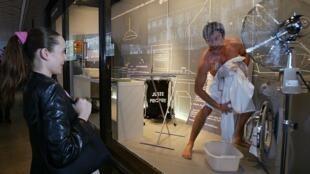 Modelo vivo na vitrine das Galerias Lafayette, em Paris, realizando tarefas domésticas.