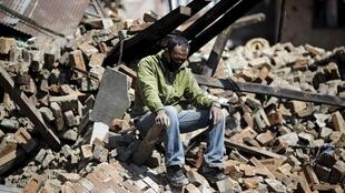 A man sits amid the ruins of his house in Kathmandu