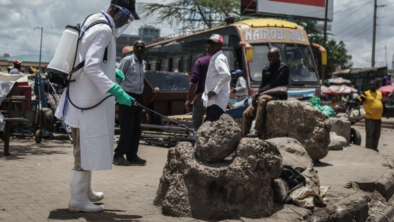 Un employé du ministère kényan de la Santé propage du désinfectant sur un rocher dans un marché de Nairobi, le 21 mars 2020.