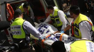 Les secours israéliens s'affairent auprès d'une victime israélienne après une attaque palestinienne contre un autobus à Jérusalem-Est en octobre 2015. Deux Palestiniens avaient ouvert le feu sur le véhicule, tuant et blessant plusieurs personnes.