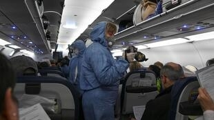 Des agents médicaux prennent la températures de passagers d'un vol au départ de l'aéroport Cheremtyevo à Moscou le 18 mars 2020.