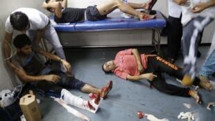 Palestinianos feridos por ataques israelitas perto do mercado de Chejaya, à espera de entrarem no Hospital de Gaza.let 2014.