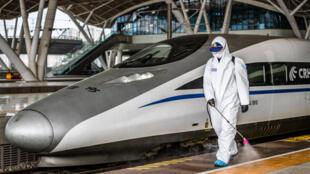 Un operario con traje protector por el coronavirus rocía con producto desinfectante un andén de la estación de trenes de Wuhan, el 24 de marzo de 2020 en la ciudad china