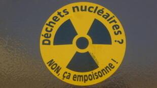 Autocollant anti-nucléaire sur une porte de maison á Bure.
