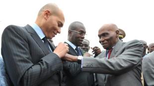 Le président Abdoulaye Wade ajuste un ruban sur le costume de son fils Karim Wade, le 19 janvier 2011.