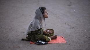 Six-year-old Abida asks for donations from pedestrians while sitting along the road in Karachi, Pakistan