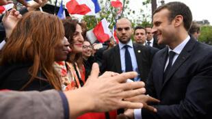 Macron cumprimenta pessoas na avenida Champs-Elysées