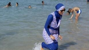 A woman wearing the body-enveloping burkini on the beach in Marseille.