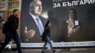 Des passants devant une affiche du parti conservateur GERB de l'ex-Premier ministre Boïko Borissov, le 24 mars 2017. mi