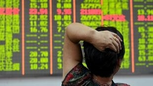 Investidor chinês observa, preocupado, o painel da  Bolsa de Valores de Hangzhou, na China, em 18 de agosto de 2015.