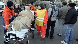 Rescue workers with a passenger from the Costa Concordia at Porto Santo Stefano