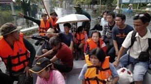 People are evacuated from a flooded village on the outskirts of Bangkok