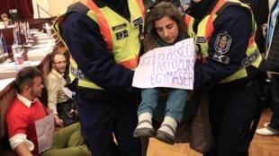 Policías húngaros expulsan de la alcaldía de Budapest a manifestantes que protestan contra esta ley, el pasado 14 de noviembre.