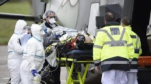 Du personnel soignant évacue un malade du Covid-19 de l'hôpital de Metz vers l'hôpital d'Essen en Allemagne le 29 mars 2020.