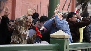 Pro-Mubarak demonstrators try to protect themselves during riots in Tahrir Square in