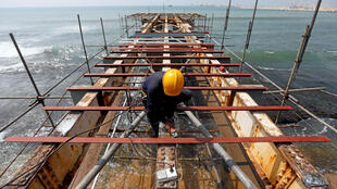 A labourer works at a construction site of a bridge on the sea in Colombo, Sri Lanka January 3, 2018. REUTERS/Dinuka Liyanawatte