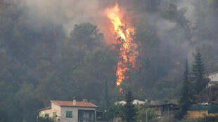 Flames approach a house during a forest fire in Castagniers near Nice