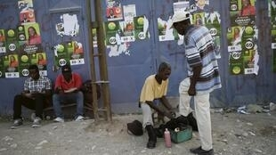 A man gets his shoes shined near posters of candidates running for legislative elections in Port-au-Prince, Haiti, August 7, 2015.