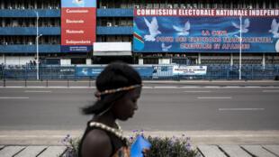 Uma mulher passa em frente da sede da Comissão Eleitoral Nacional Independente, em Kinshasa. Imagem de ilustração