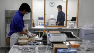 Des laborantins découpent du poisson pour des tests de radiation dans le port de Matsukawaura à Soma, dans la préfecture de Fukushima, le 20 février 2019.