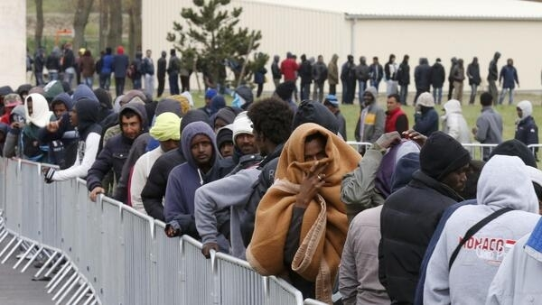 Migrants cue for a meal in Calais, some will ask for asylum in France.