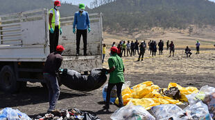 Debris is loaded onto a truck at the crash site of the Ethiopian Airlines operated Boeing 737 Max aircraft, at Hama Quntushele village in the Oromia region, 13 March 2019.