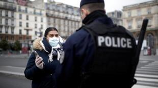 """法國宣布封城後,所有人出門都要隨身攜帶從網上下載的""""通行證""""。這是巴黎警察正在盤問路人。"""