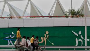 Labourers ride a rickshaw in front of the Jawaharlal Nehru Stadium in New Delhi.