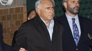 Dominique Strauss-Kahn saindo algemado da delegacia do Harlem, no domingo 15 de maio.