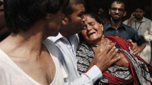 Mulher chora a morte de familiar após ataque a igreja no Paquistão.