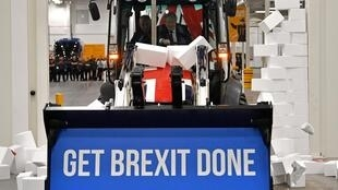 "Britain's Prime Minister and Conservative party leader Boris Johnson drives a Union flag-themed JCB, with the words ""Get Brexit Done"" inside the digger bucket, through a fake wall emblazoned with the word ""GRIDLOCK"", during a general election campaign"