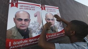 Líbio cola cartazes de Ali Kulaish, candidato às eleições parlamentares em Benghazi, nesta quarta-feira.