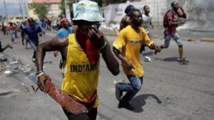 Des manifestants fuient les forces de sécurité, lors d'une manifestation réclamant la démission du président haïtien Jovenel Moïse à Port-au-Prince, le 27 septembre 2019.
