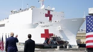Le président américain Donald Trump salue l'équipage du navire hôpital USNS Comfort à Norfolk, le 28 mars. Le navire doit arriver à New York ce lundi 30 mars.