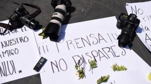 Las cámaras de algunos fotógrafos soportan carteles en los que se pide respeto y libertad a la prensa en México tras la ola de asesinatos de periodistas que azota al país.  REUTERS/Yahir Ceballos