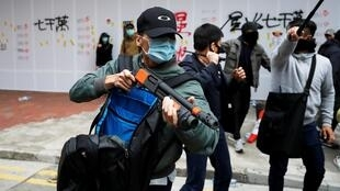 A heavily-armed plain-clothes police officer helping to disperse anti-government protesters in Hong Kong.