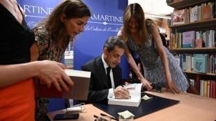 L'ancien président français Nicolas Sarkozy (c) signe son livre aux côtés de son épouse Carla Bruni-Sarkozy (d), dans une librairie à Paris, le 28 juin 2019.