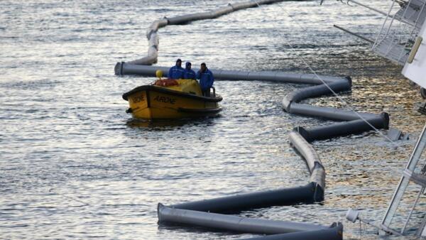 Guarda costeira e operários reúnem esforços para distribuir barreiras de proteção a vazamento de combustível proveniente do navio Costa Concordia no litoral da Ilha de Giglio, nesta quarta-feira.