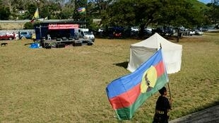 """حمل پرچم استقلالطلبان کالدونیاینو توسط یک کودک، در جلسه این گروه، در شهر """"نومِه آ"""" پایتخت این کشور.  ."""