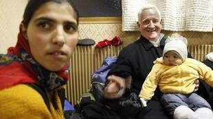 French priest Father Arthur Hervet with a Roma family in Villeneuve d'Ascq in December 2009
