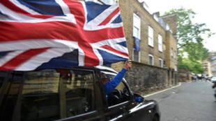 A taxi driver holds a Union flag, as he celebrates following the result of the EU referendum, in central London A taxi driver holds a Union flag, as he celebrates following the result of the EU referendum, in central London, Britain June 24, 2016.