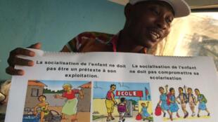 Denis Tindji Logbou, president de la coopérative de Guitry (département de Divo), expose le kit pédagogique contre le travail des enfants dans les plantations de cacao.