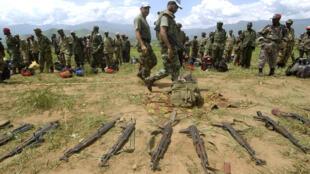Des soldats de l'ONU inspectent des armes des FDLR dans un camp de désarmement.