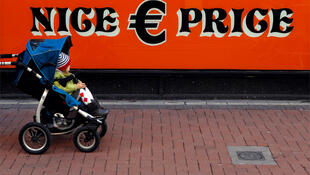 A pram is pushed past a discount store in central Dublin